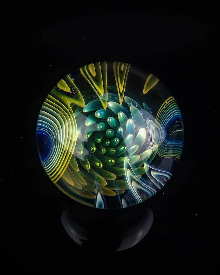 Artist Adam Smolensky creates art glass marbles that contain tiny worlds within